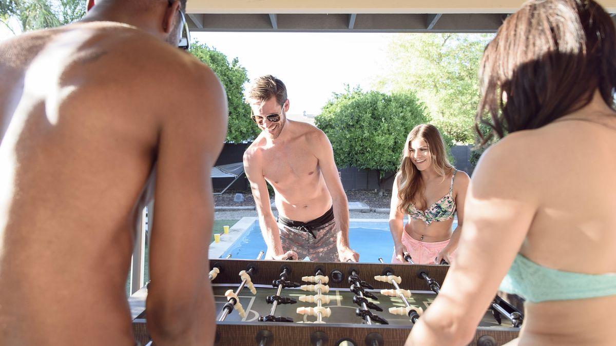 Jugend in Badehose und Bikini beim Tischfußball im Schweimmbad