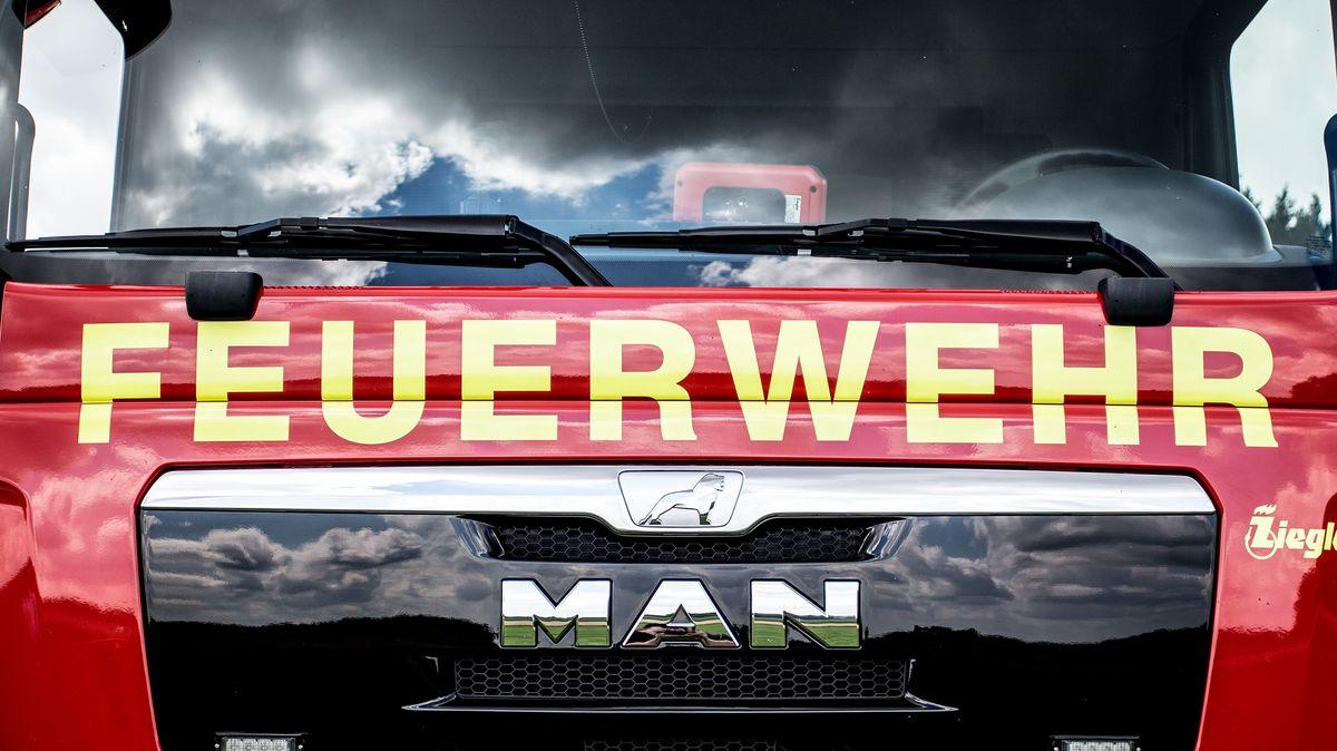 Feuerwehrfahrzeug. In der Scheibe spiegeln sich dunkle Gewitterwolken (Symbolbild)