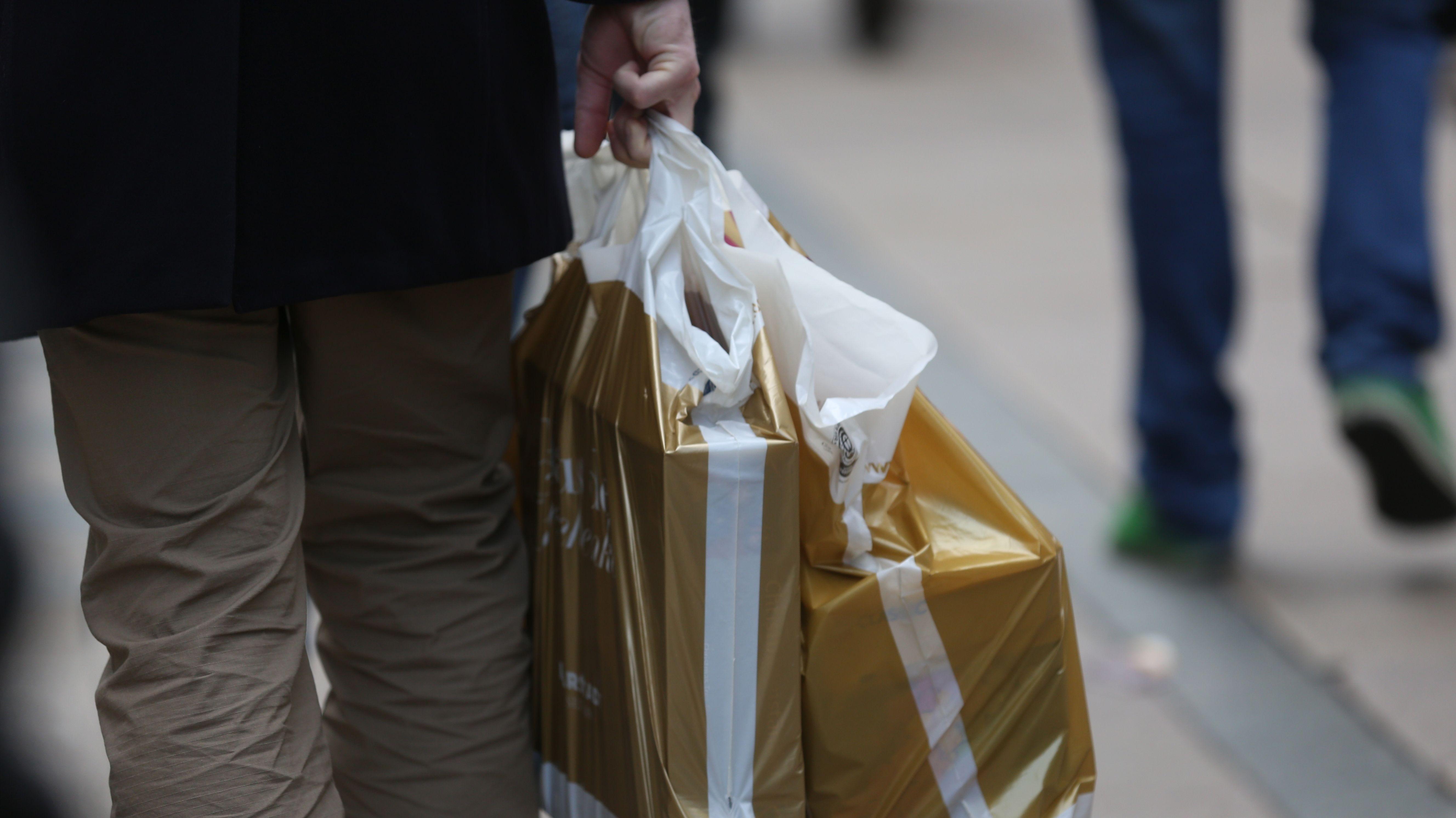 Person trägt zwei gold-weiße Einkaufstüten aus Plastik.