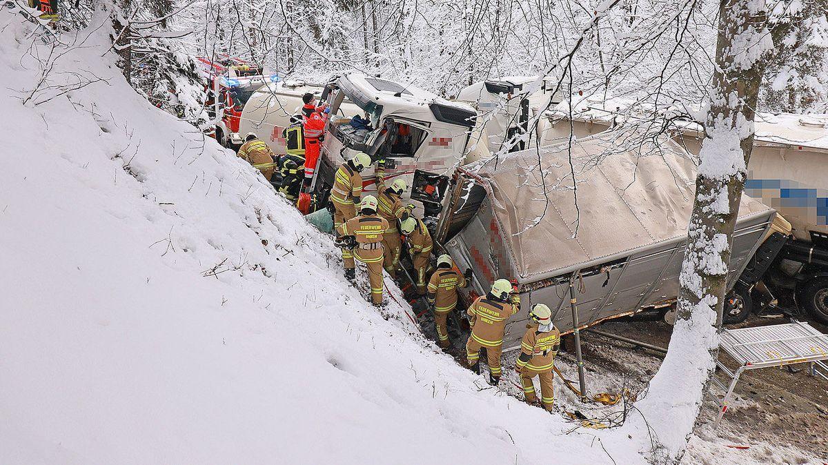 Feuerwehrmänner und Kräfte des Bayerischen Roten Kreuzes bergen die umgekippten Lastwagen.
