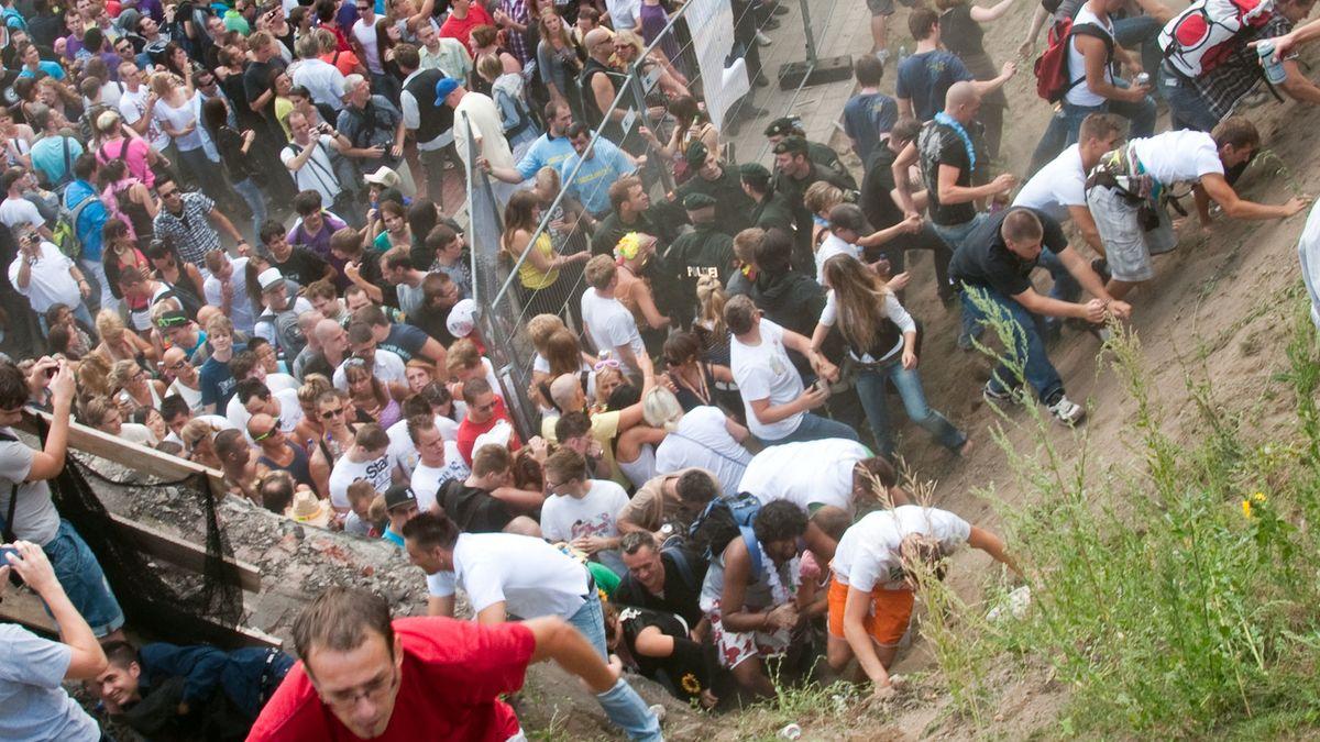 Menschen klettern verzweifelt einen Abhang herauf um den Gedränge auf dem Laveparade-Gelände zu entkommen