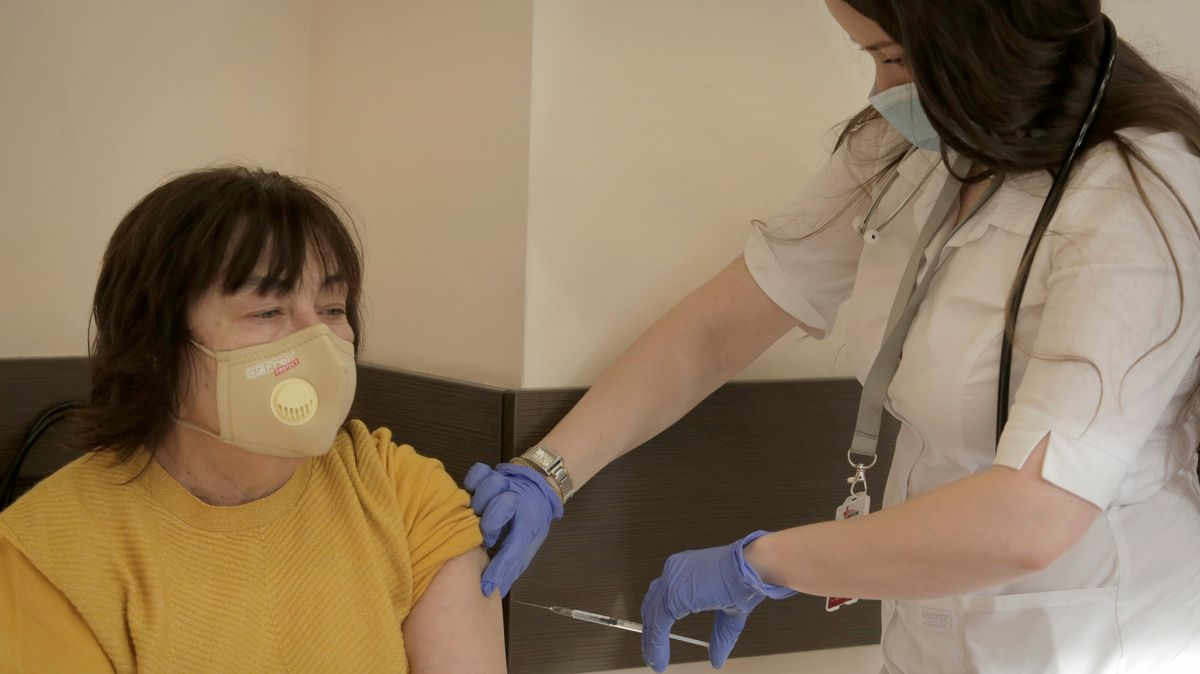 Eine Frau erhält von einer Mitarbeiterin des Gesundheitswesen eine Corona-Impfung.