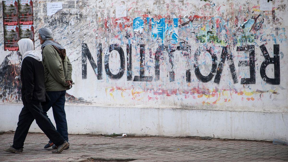 """Tunesien, Sidi Bouzid: Anwohner gehen an einer Mauer vorbei, auf der das Wort """"Revolution"""" auf dem Kopf steht."""