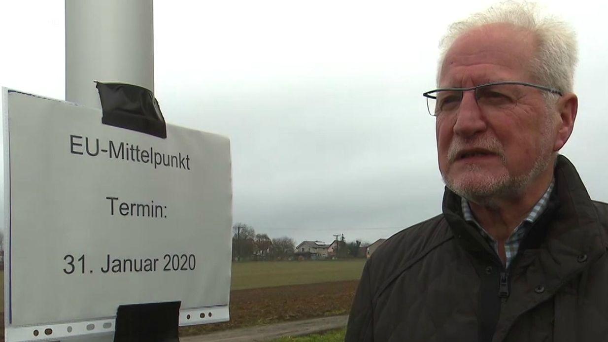Walter Dieck, Gadheimer Ortssprecher, steht vor dem Masten des neuen EU-Mittelpunkts