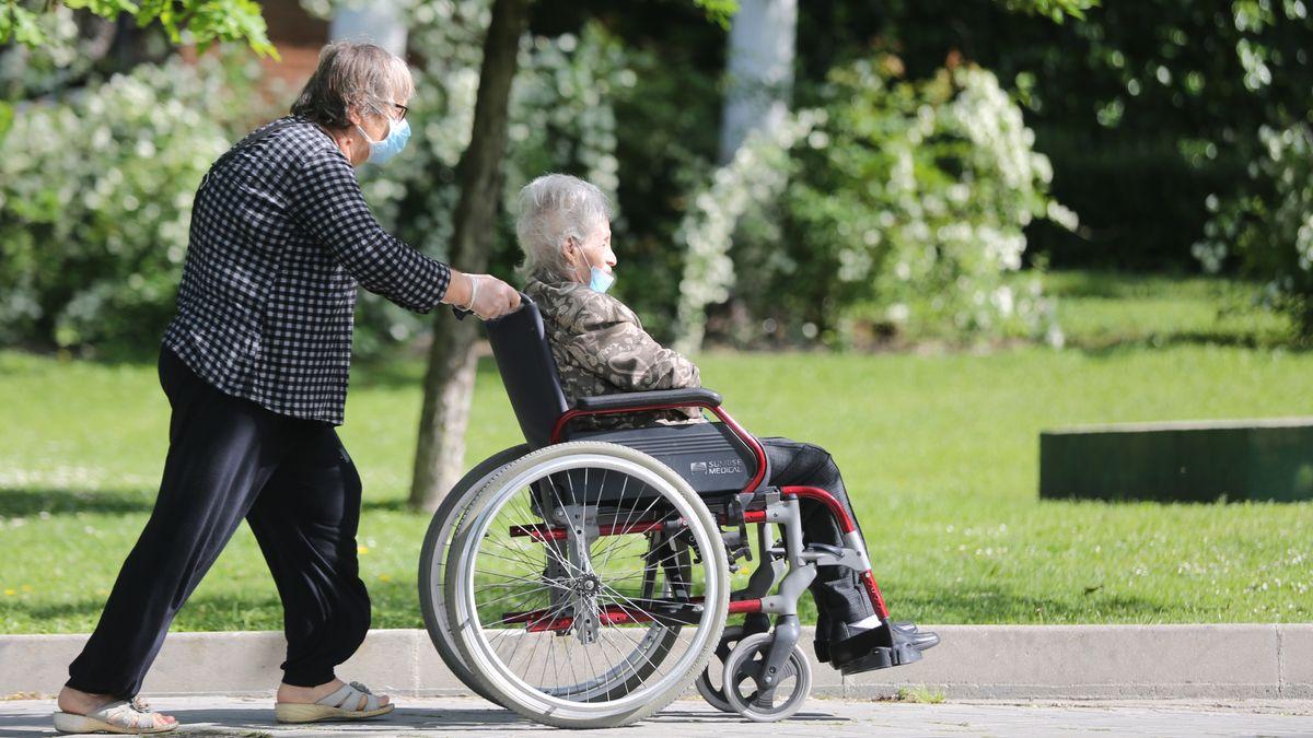 Ein Mann schiebt eine ältere Frau im Rollstuhl, beide tragen einen Mundschutz