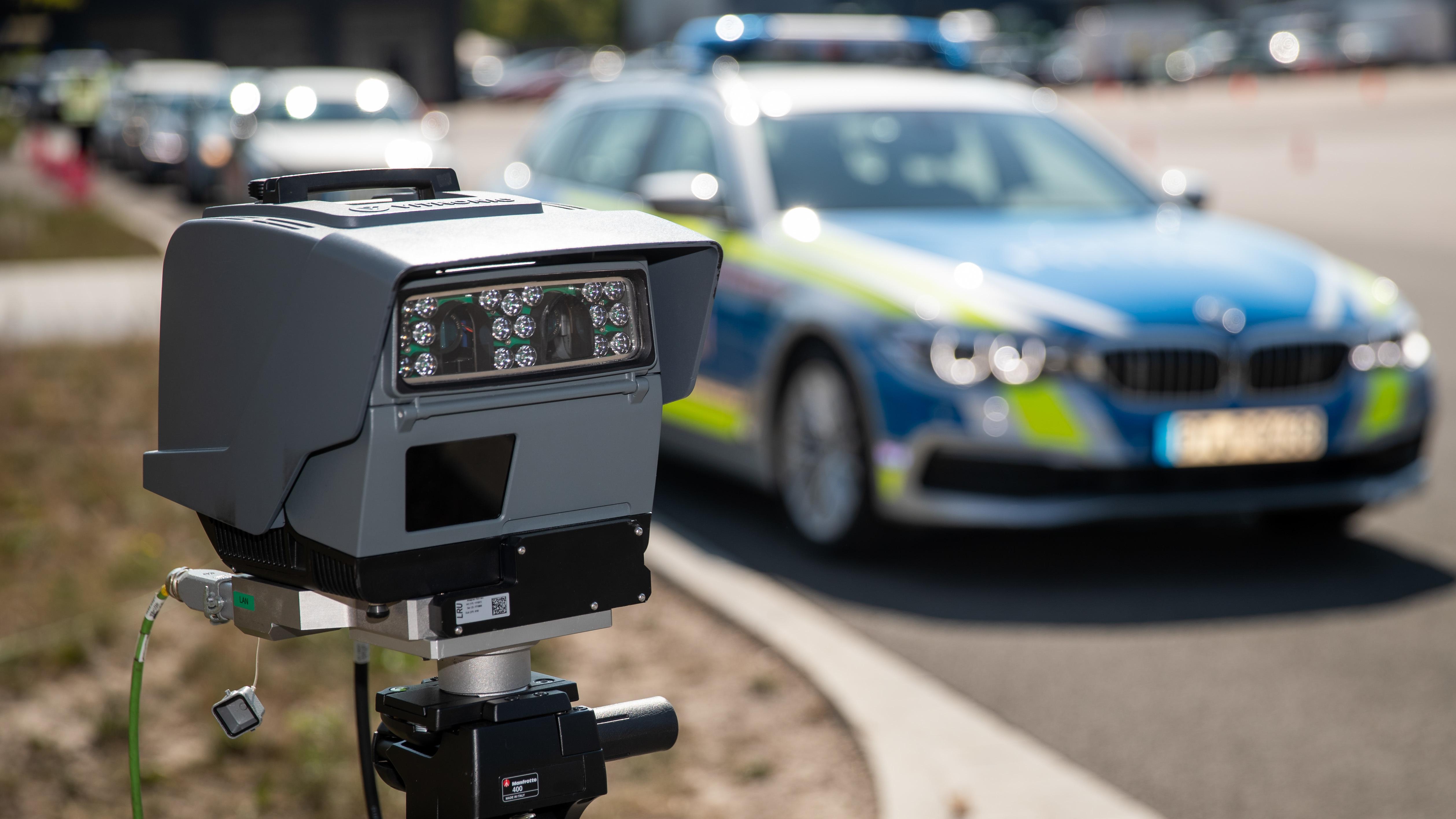 Eine transportable automatisierte Kennzeichenerkennungs-Anlage (AKE) steht vor einem Polizeiauto.