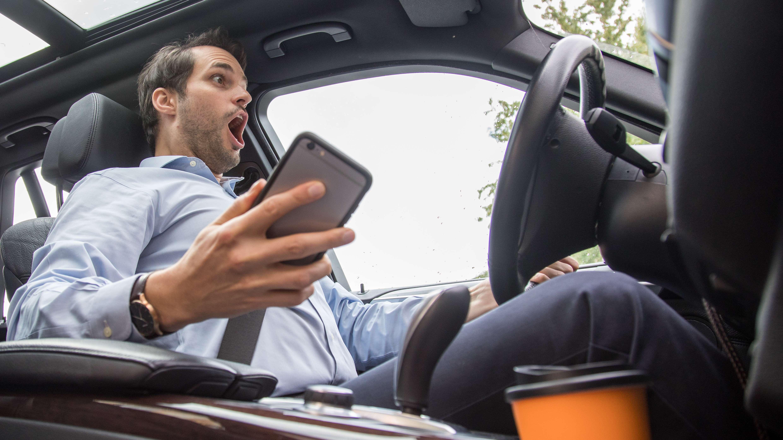 Ein Mann greift in seinem Auto nach seinem Smartphone (gestellte Szene).