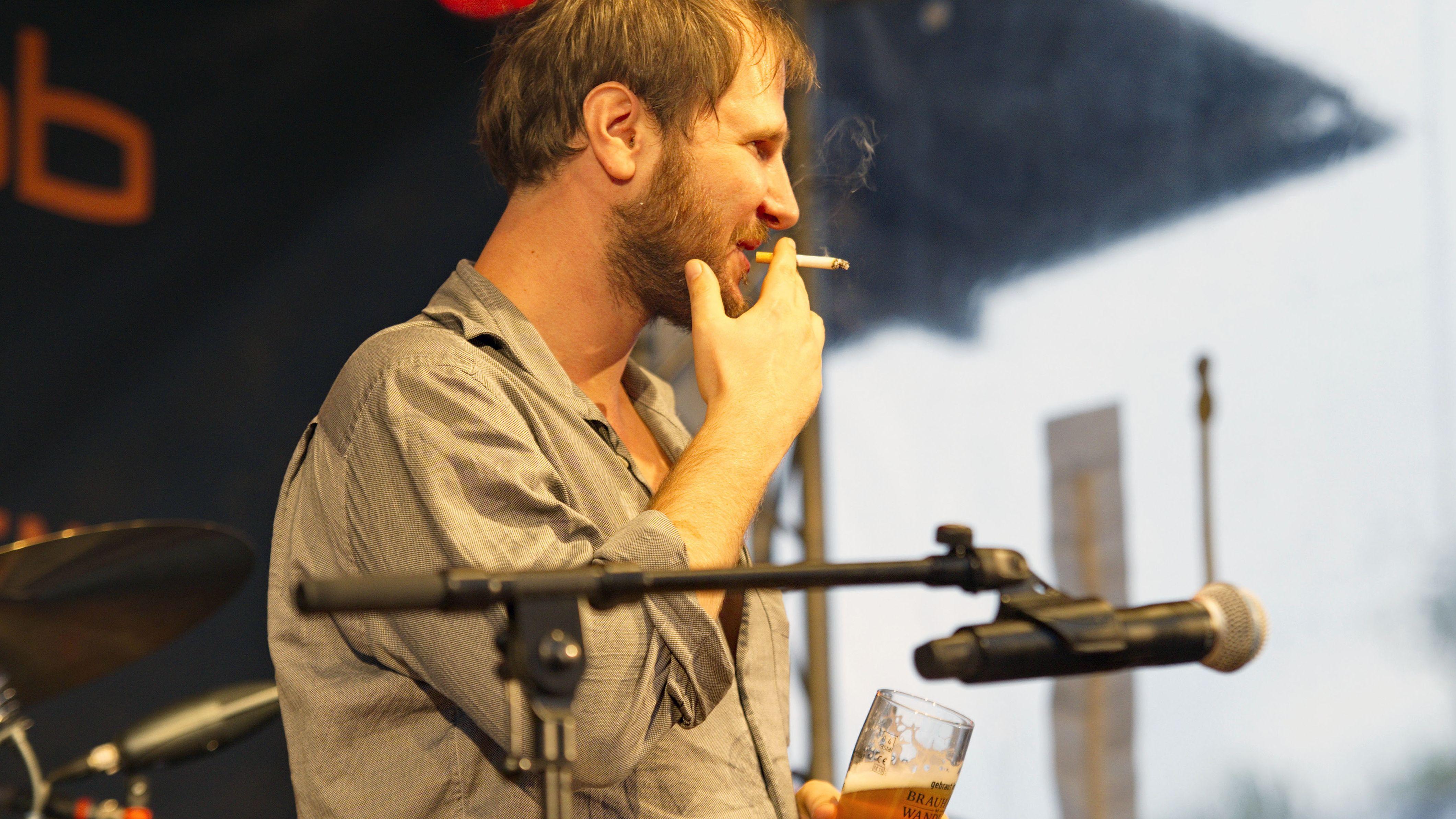 Der Sänger von Wanda steht bei einem Auftritt in Berlin rauchend und mit Bier auf der Bühne.