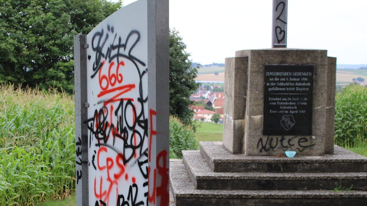 Beschmierte Infotafel und Denkmal