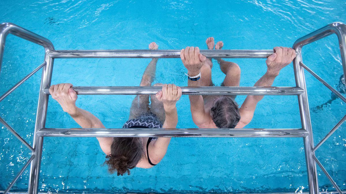 Badegäste hängen in einem Schwimmbad über dem Wasser an einem Gerüst.