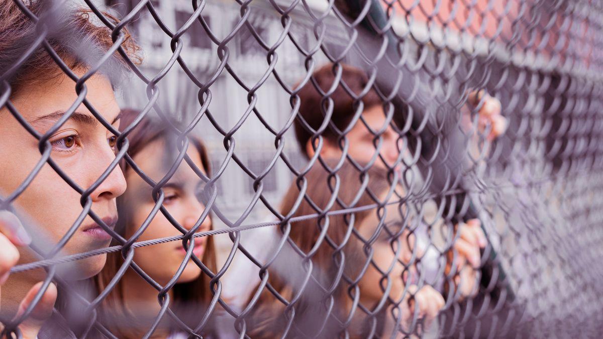 Jugendliche schauen durch einen Maschendrahtzaun.