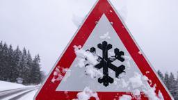 Ein schneebedecktes Verkehrsschild warnt vor Straßenglätte   Bild:dpa-Bildfunk