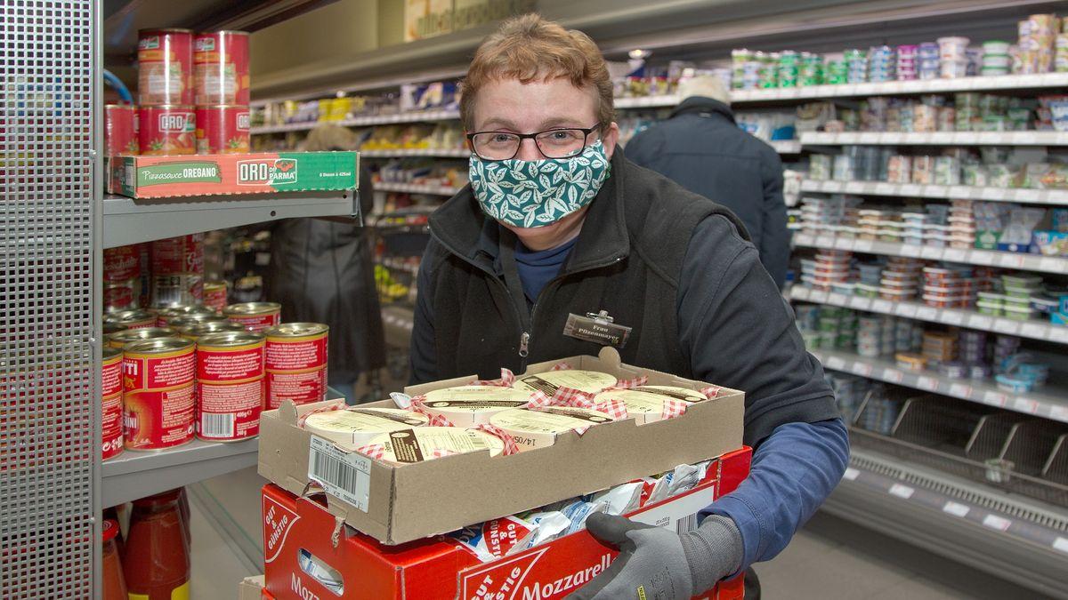 Mitarbeiterin in Supermarkt füllt Regale auf