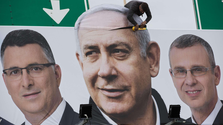 Ein Mann bringt ein Wahlplakat mit Ministerpräsident Benjamin Netanjahu und zwei weiteren Kandidaten an.