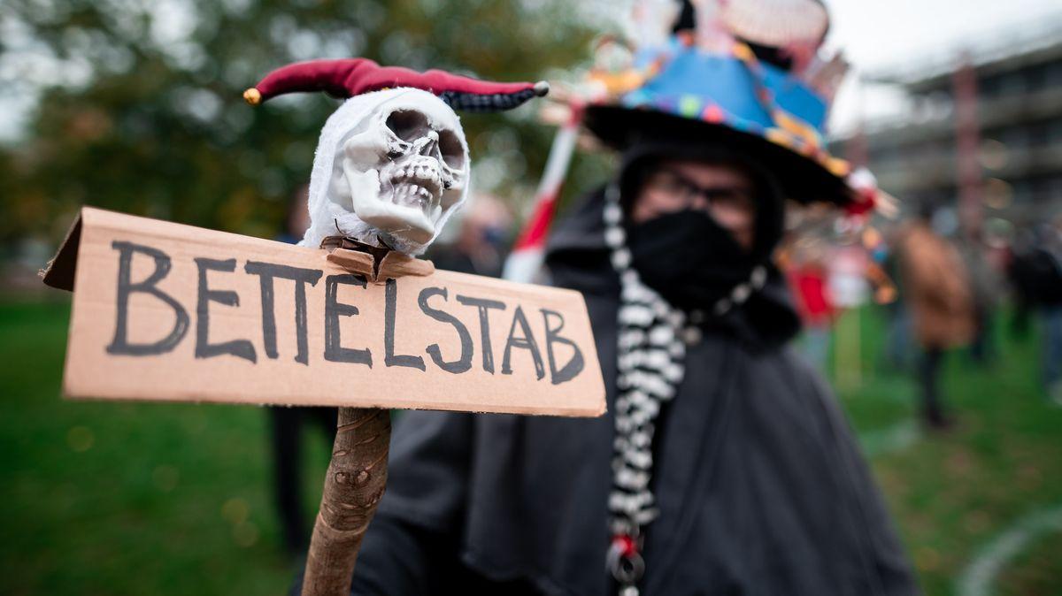 """Demonstrant mit einer """"Bettelstab""""-Figur mit Totenkopf."""