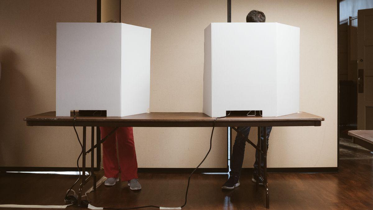 Zwei Wahlkabinen in North Carolina. Dahinter stehen zwei Menchen.