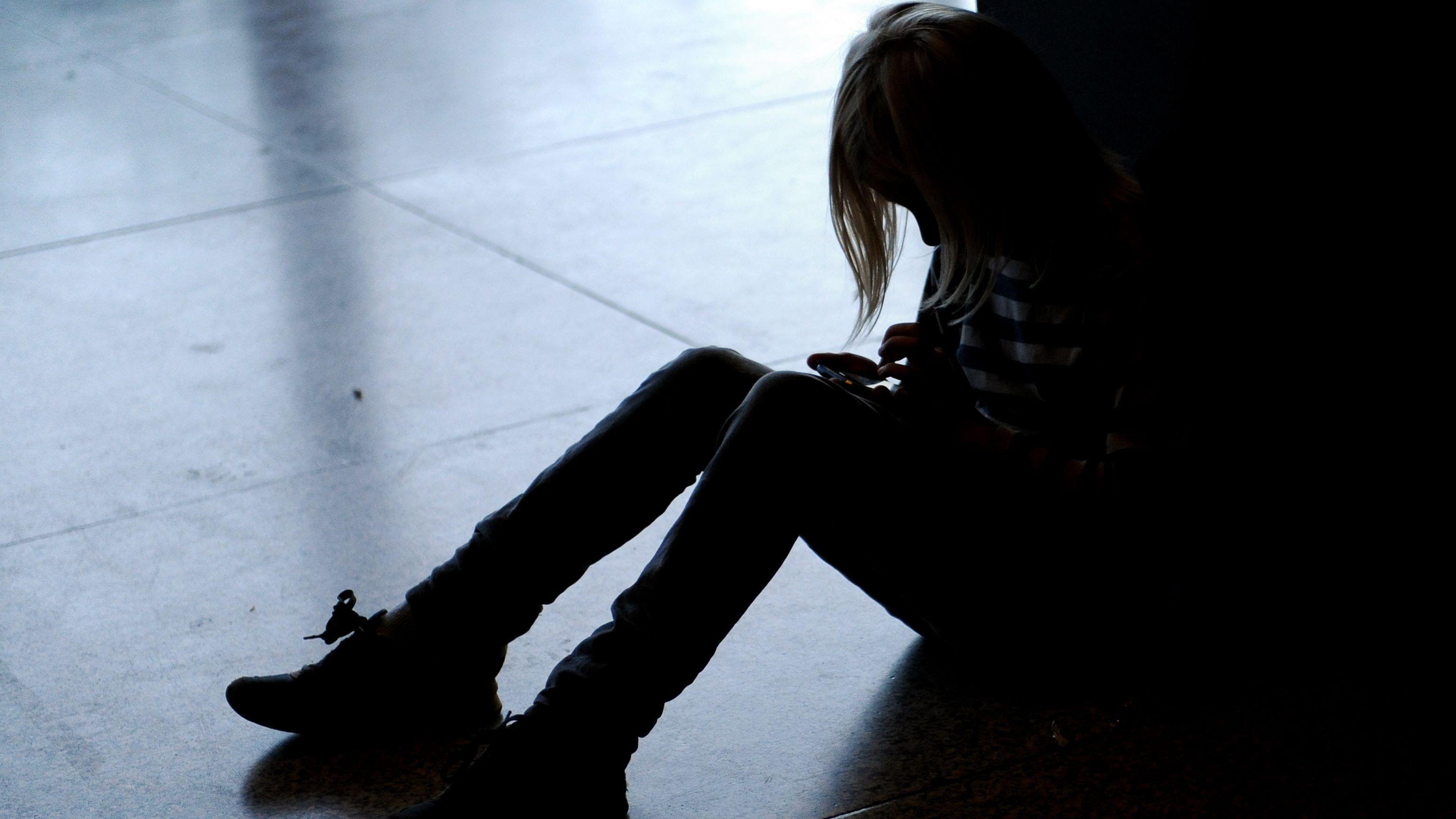 Ein kleines Mädchen sitzt allein auf dem Fußboden und hat den Kopf gesenkt.