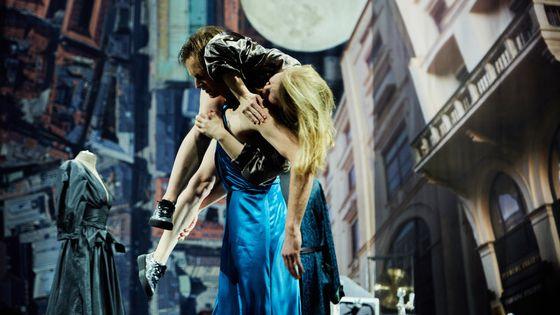 """""""Im Dickicht der Städte"""" Münchner Kammerspiele: Ein Mann trägt eine Frau vor einer Stadtkulisse"""