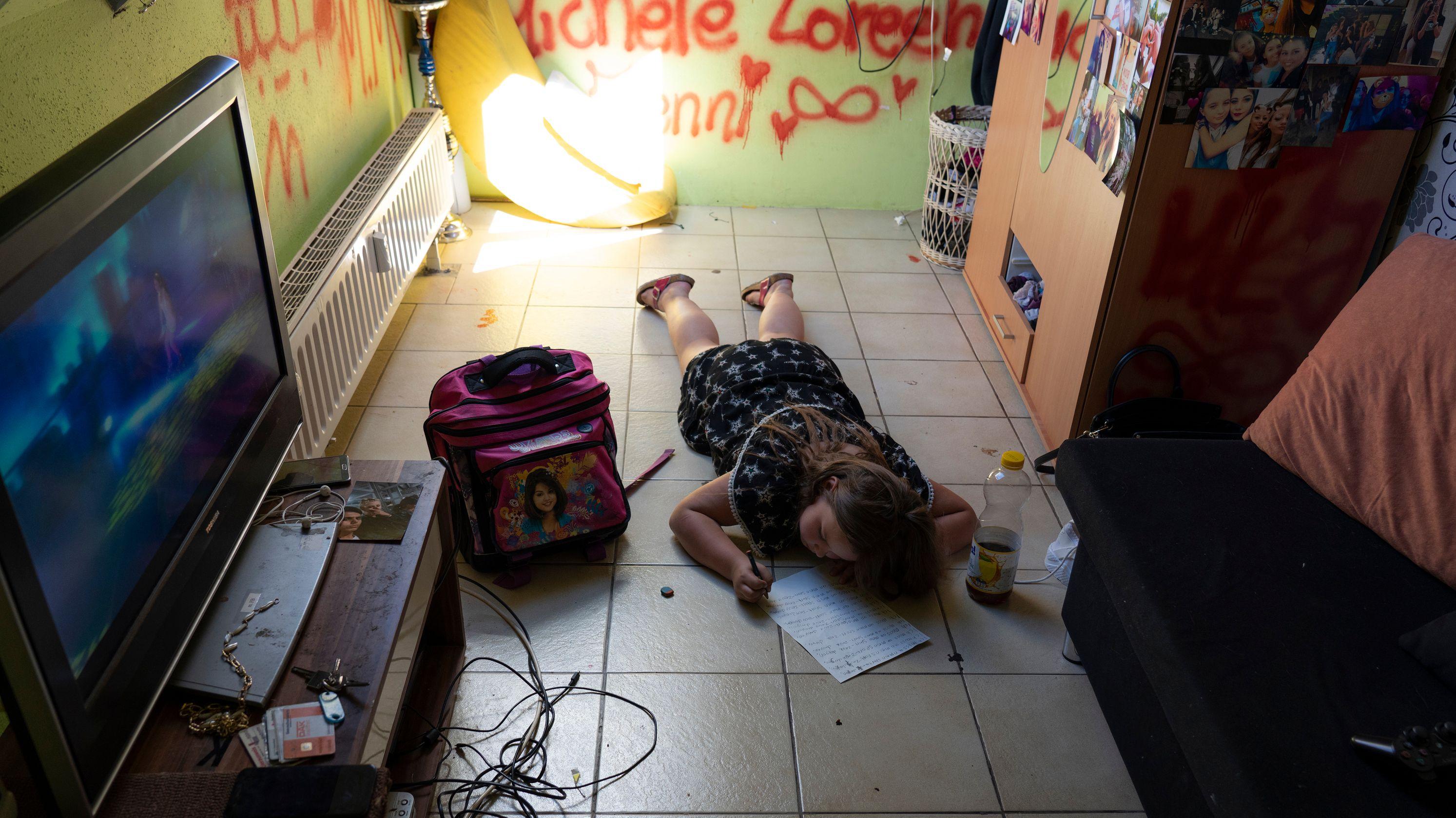 Ein Mädchen liegt in einem unordentlichen Raum unter Graffiti auf dem Boden und schreibt in ein Schulheft
