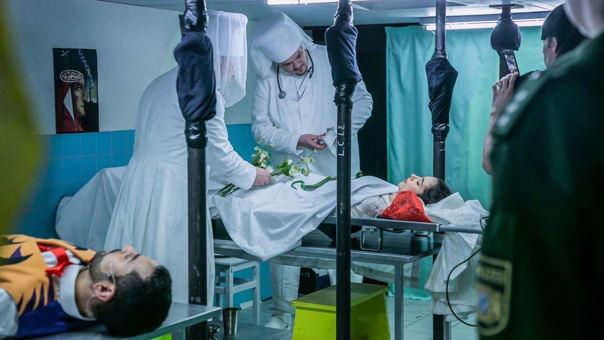 Ärzte in weißen Kitteln beugen sich über eine Bahre, auf der eine junge Frau liegt