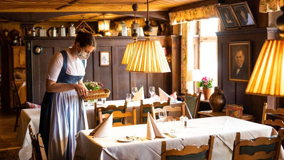 Frau deckt einen Tisch im Restaurant ein.  | Bild:dpa-Bildfunk / Philipp von Ditfurth