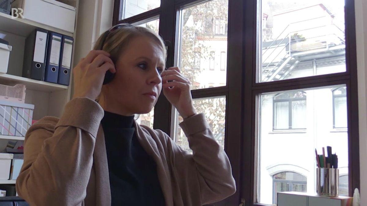 Eine Frau sitzt mit einem Headset auf dem Kopf in ihrem Arbeitszimmer