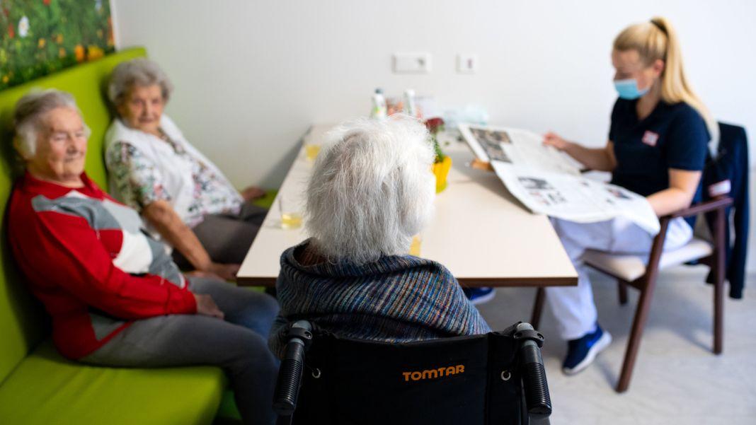 Eine Pflegerin mit Maske liest drei Seniorinnen aus der Zeitung vor.