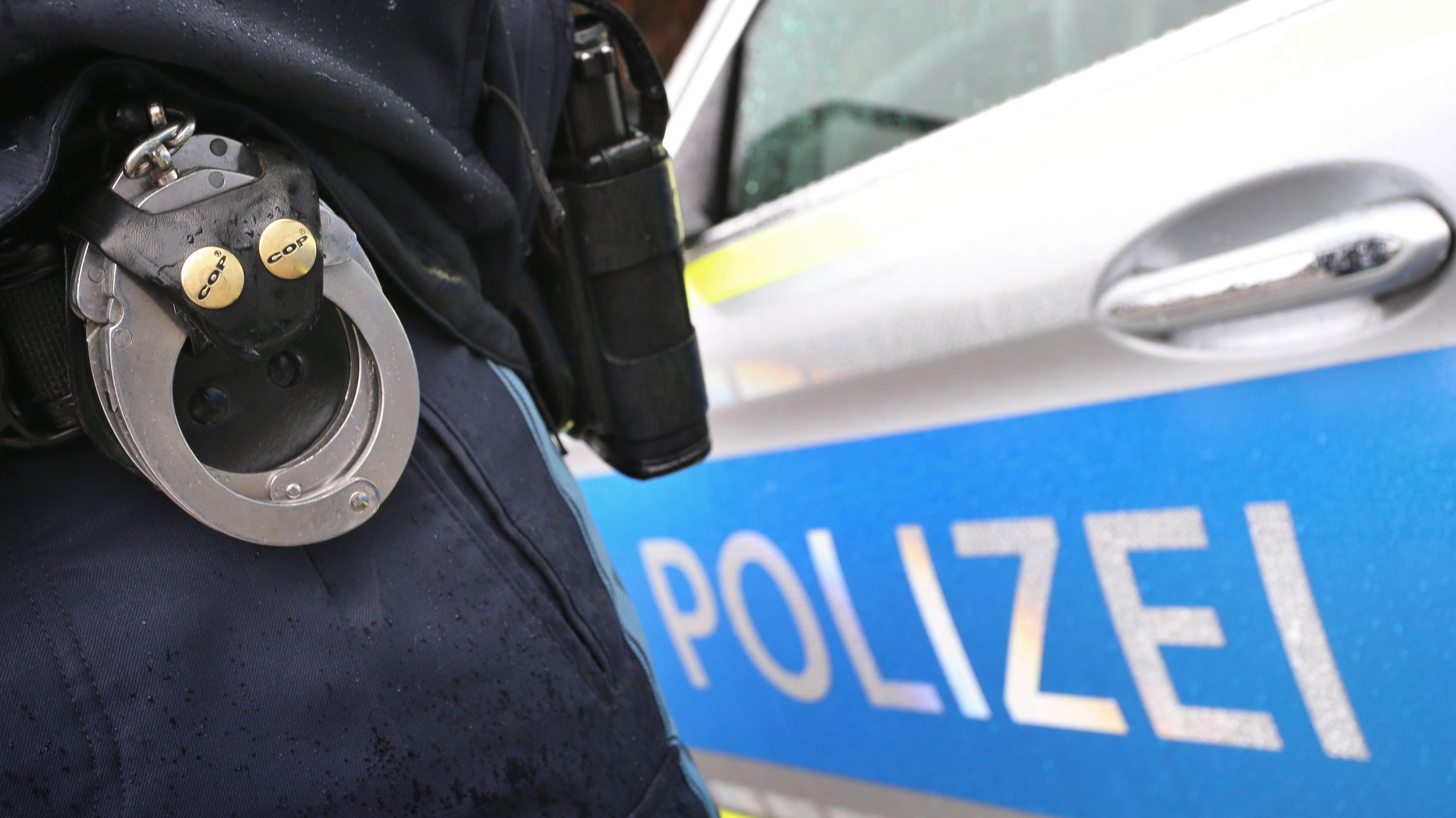 Ein Polizist mit Handschellen und Pistole steht neben einem Einsatzwagen.