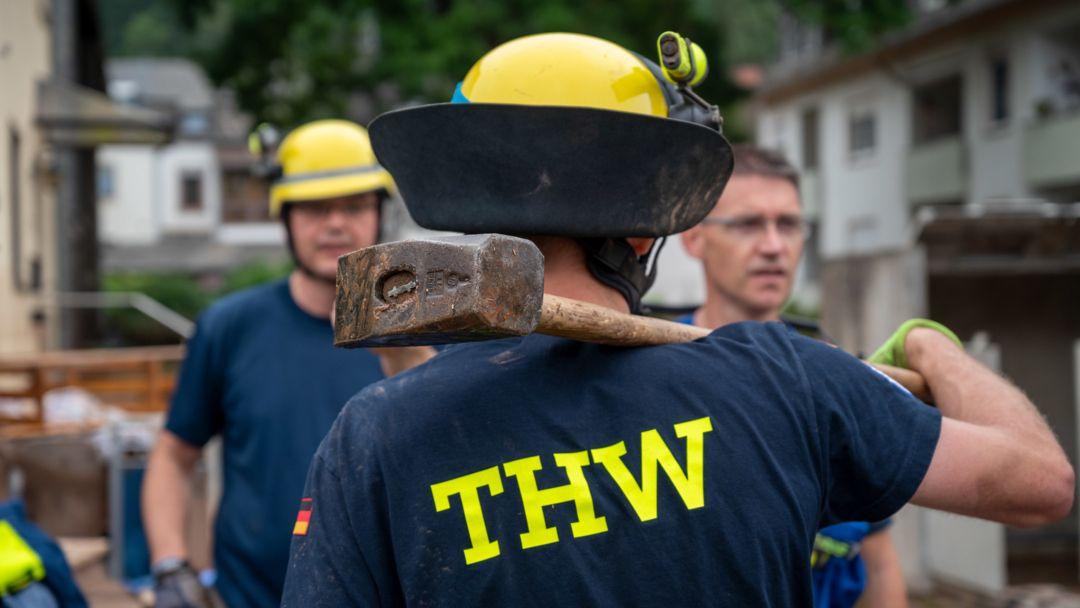 Bei Aufräumarbeiten steht ein THW-Helfer mit einem Vorschlaghammer in einem vom Hochwasser beschädigten Wohngebiet