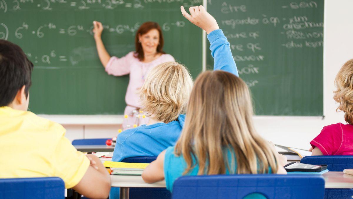 Lehrerin beim Unterricht vor Schulklasse