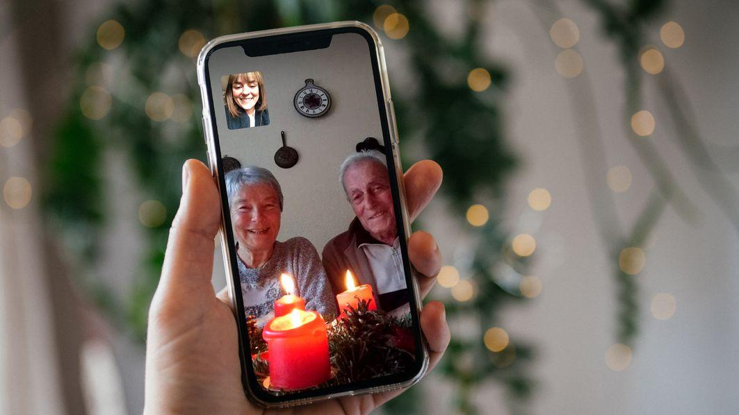 Eine Frau und ihre Großeltern feiern Weihnachten zusammen übers Handy.