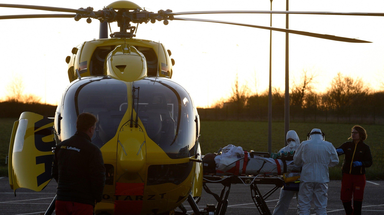 Zwei Medizinier in weißen Schutzanzügen schieben Corona-Patienten auf Bahre in Notarzt-Hubschrauber