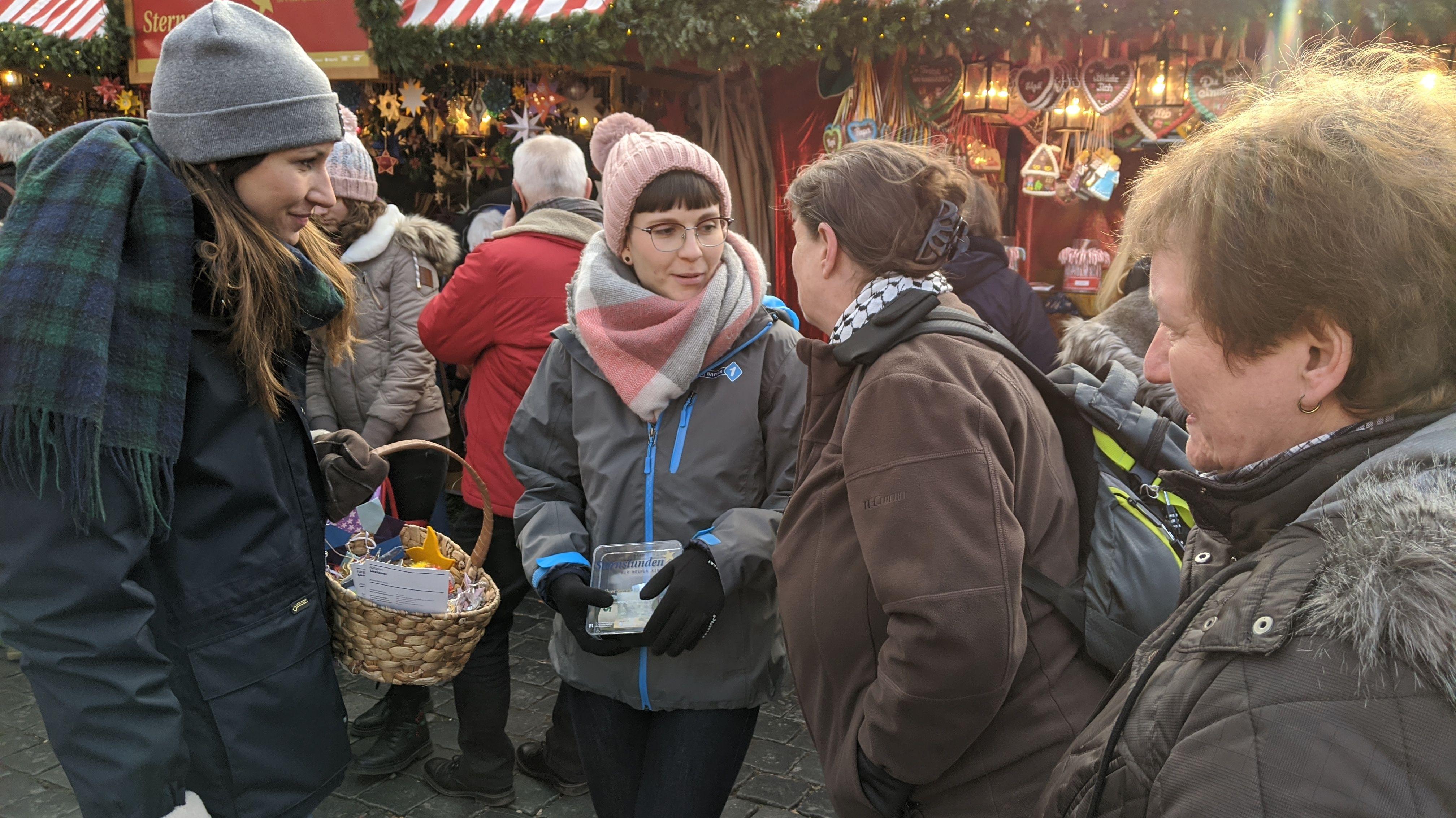 Laura Grun und Annika Svitil mit Sternekörbchen und Spendenbüchse im Gespräch mit Besucherinnen.