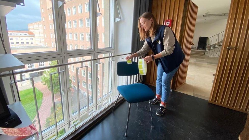Eine Frau klebt einen Sticker auf einen Stuhl