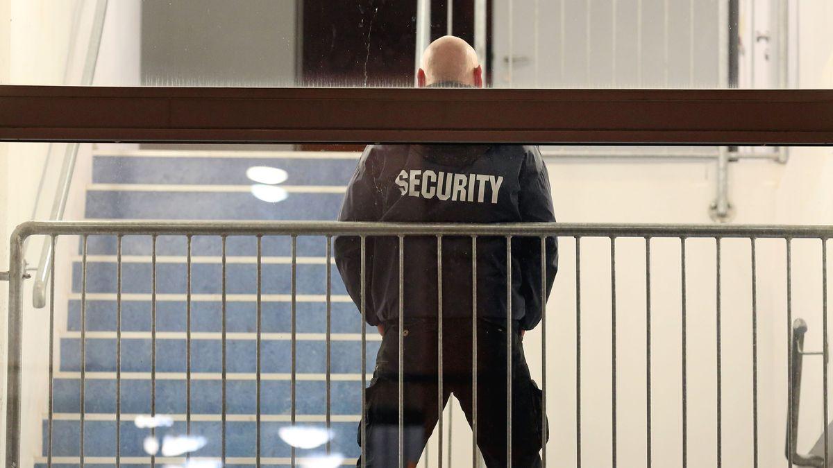 """Symbolbild Sicherheitsdienst - """"Security"""" steht auf der Jacke eines glatzköpfigen Mannes, der hinter einer Absperrung steht"""
