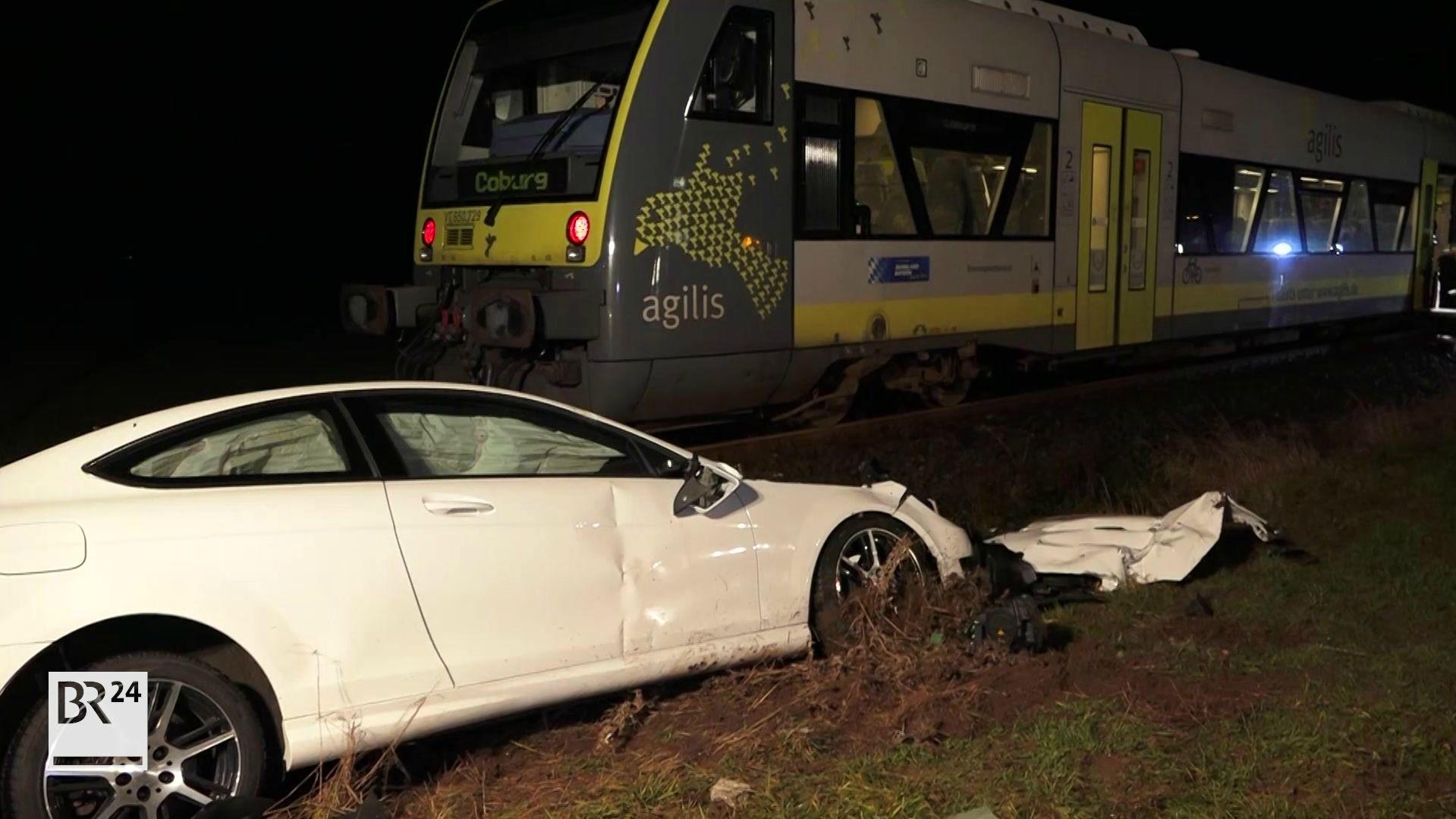 Ein weißes auto liegt neben einem Zug beschädigt im Feld.