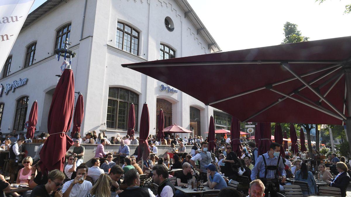 """Bayern, München: Gäste sitzen vor dem Restaurant """"Schrannenhalle"""" und genießen das schöne Wetter."""