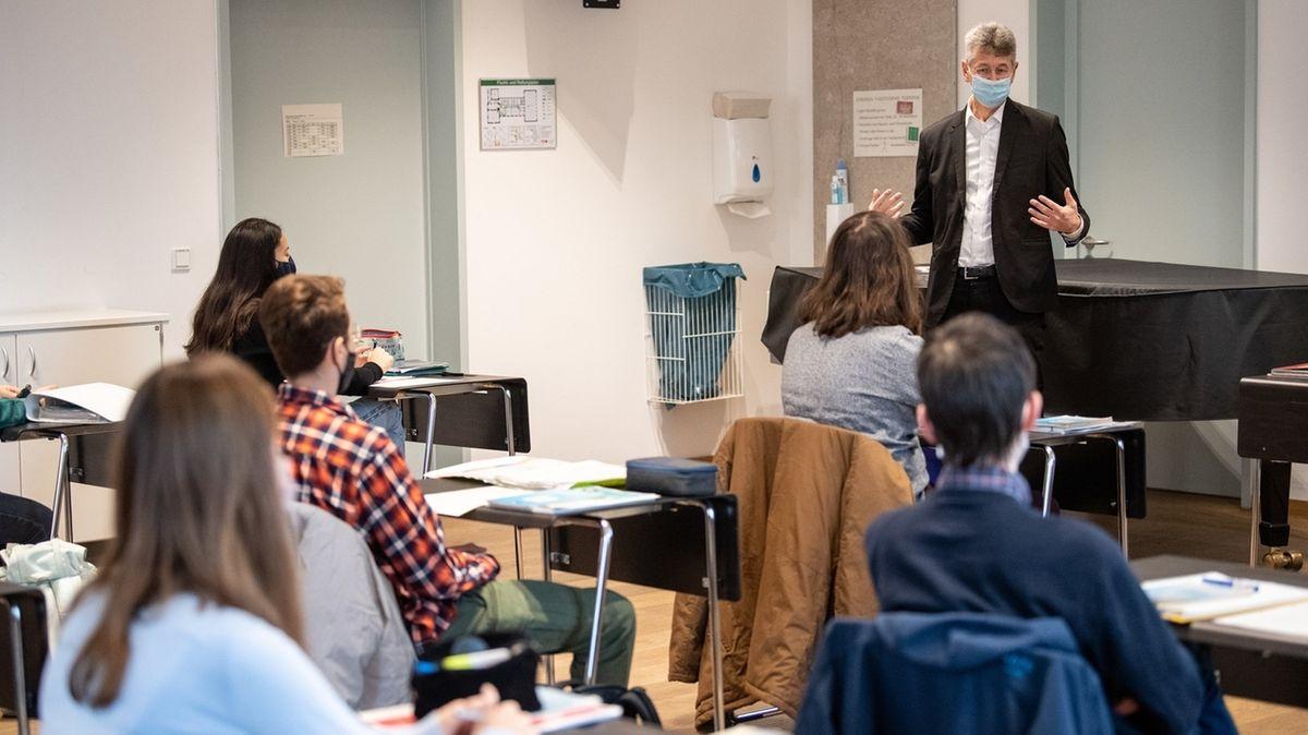 Bayerns Kultusminister Michael Piazolo spricht mit Schülerinnen und Schülern in einem Münchner Gymnasium