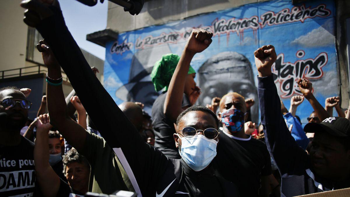 Demonstrierende Schwarze mit Mundschutz recken auf einer Demo ihre Fäuste in den Himmel