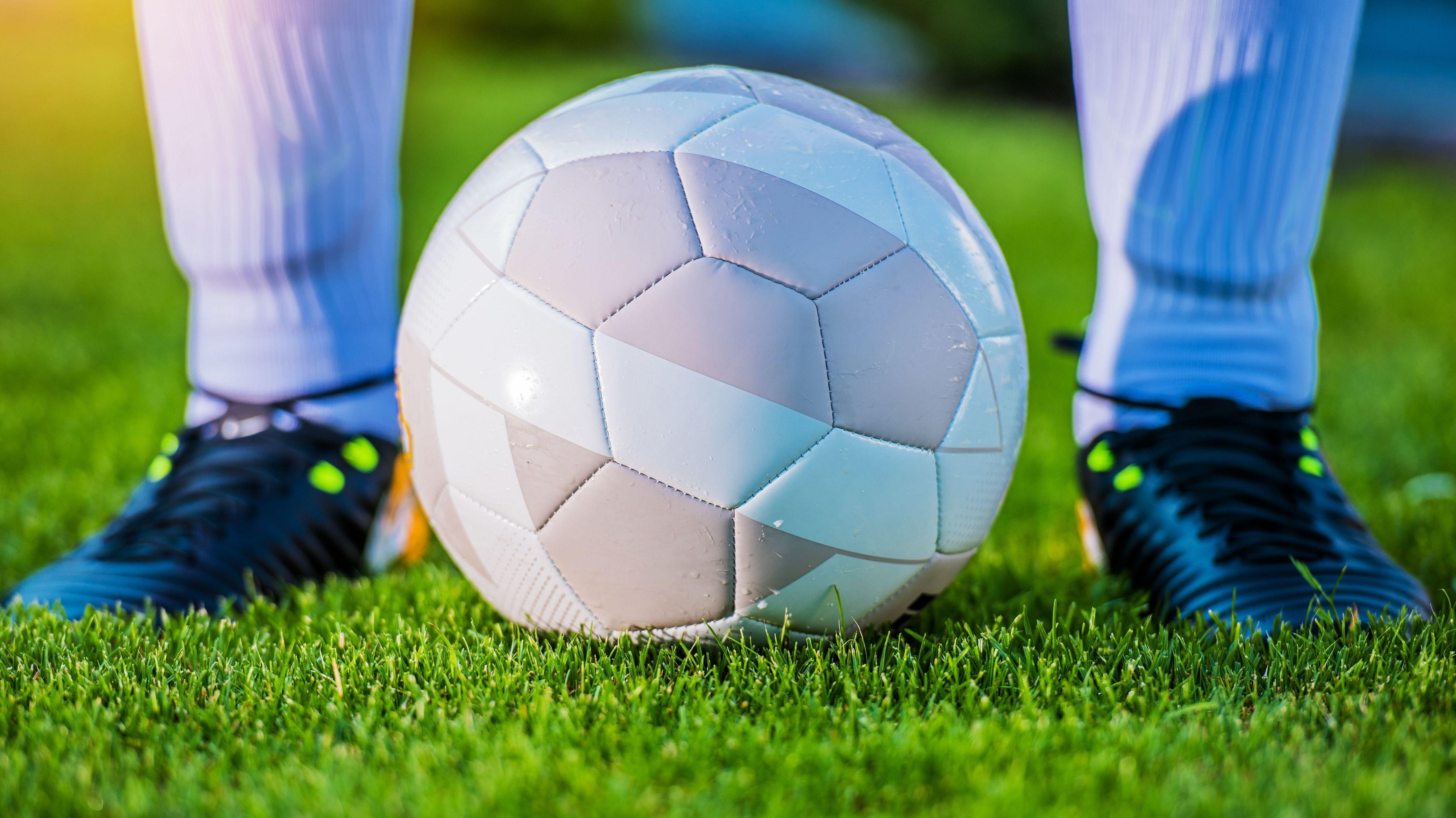 Symbolbild: Fußball und Fußballschuhe