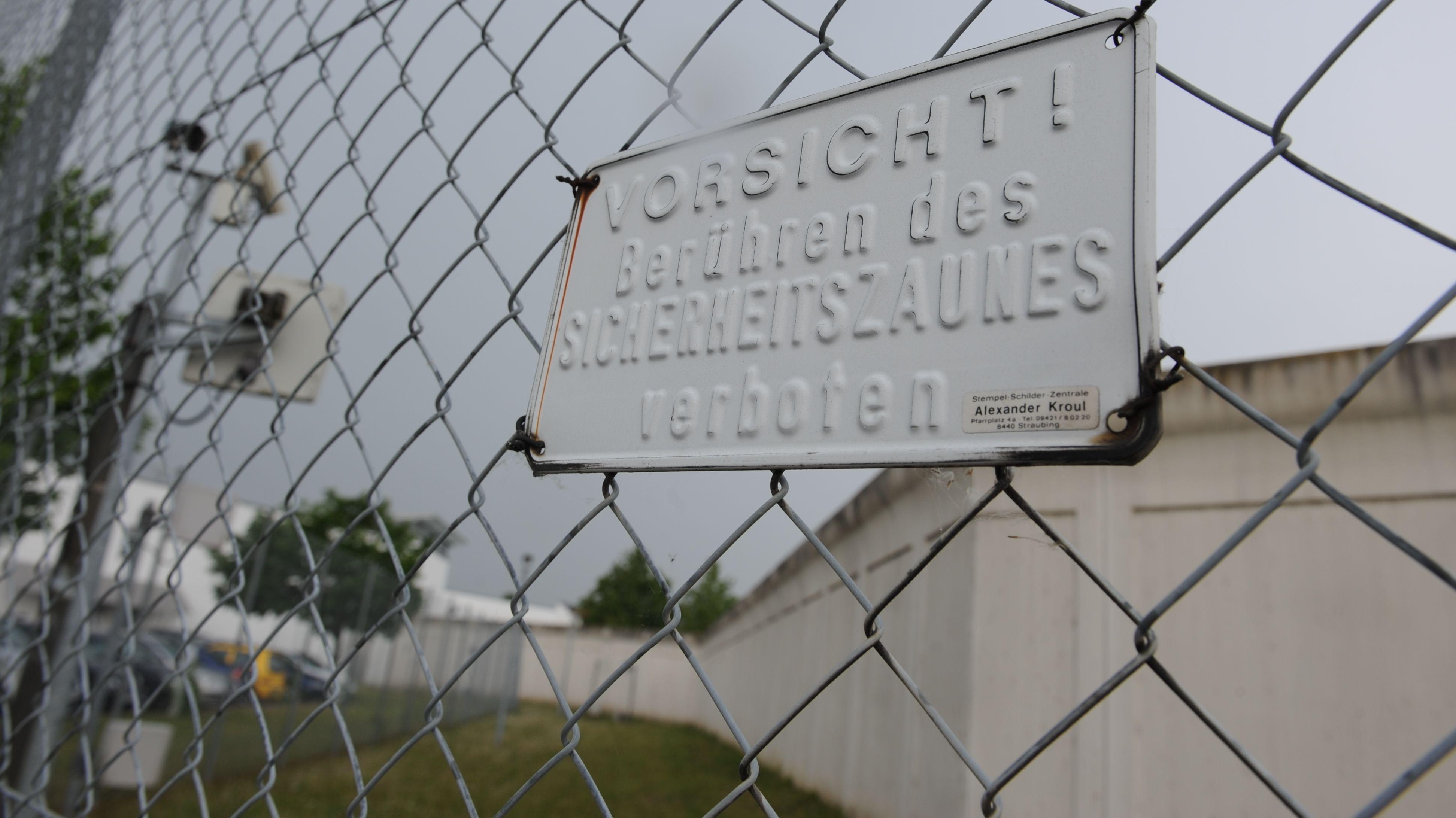 """Ein Schild mit der Aufschrift """"Vorsicht! Berühren des Sicherheitszaunes verboten"""", am Zaun vor der Mauer des BKH in Straubing"""