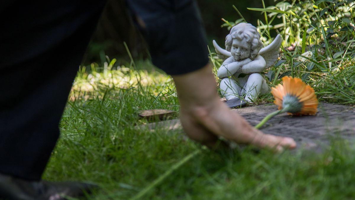 Frau legt Blume auf Grab
