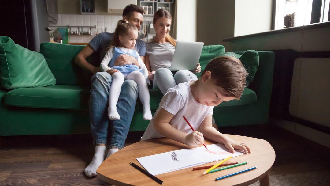 Eltern sitzen mit ihrer Tochter auf einem grünen Sofa und blicken gemeinsam aufs Laptop. Ihr Sohn kniet vor dem Couchtisch und malt ein Bild.