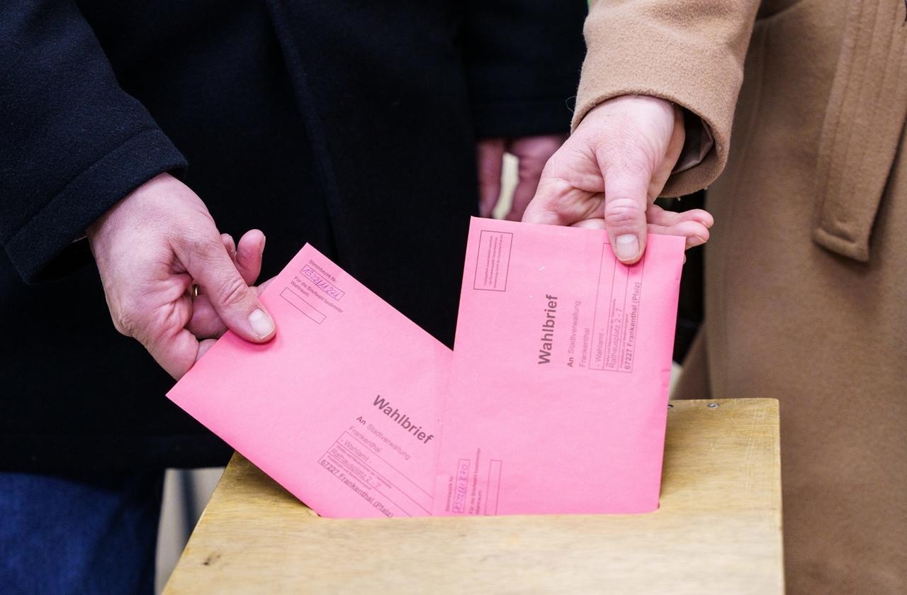 08.03.2021, Rheinland-Pfalz, Frankenthal: Christian Baldauf (CDU), Spitzenkandidat seiner Partei zur Landtagswahl 2021, und Frau Martina Baldauf stecken in einem Briefwahlbüro Wahlbriefe mit ihrer Stimme in eine Wahlurne. Der Spitzenkandidat der CDU-Rheinland-Pfalz hat im Briefwahlbüro in Frankenthal seine Stimme abgegeben. Die Landtagswahl in Rheinland-Pfalz soll am 14. März 2021 stattfinden. Foto: Andreas Arnold/dpa +++ dpa-Bildfunk +++