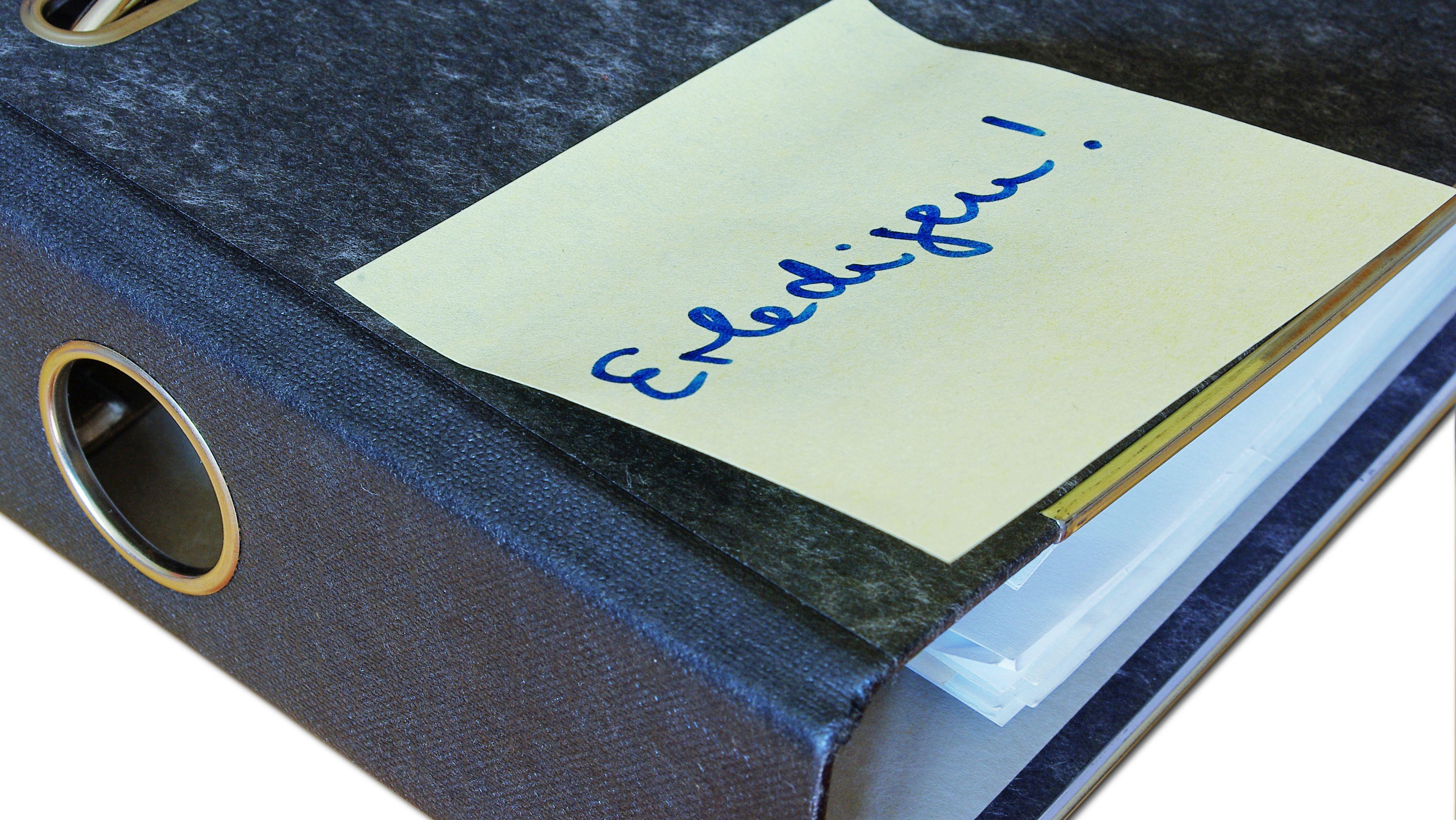 """Post-it mit dem Schriftzug """"Erledigen!"""" auf einem Aktenordner"""