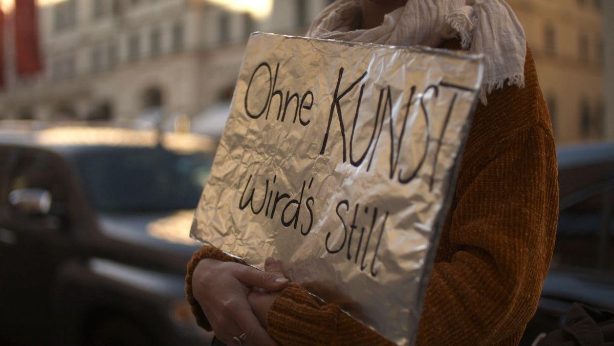 """Ein selbst gemaltes Schild mit der Aufschrift """"Ohne Kunst wird's still""""."""