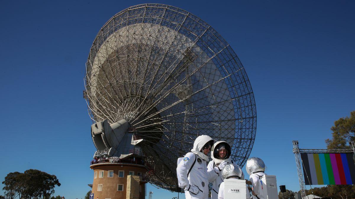 Eine Besuchergruppe steht verkleidet als Astronauten von dem Parkes Teleskop in Australien.