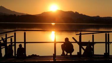 Füssen: Menschen genießen am Ufer des Hopfensees den Sonnenuntergang. Foto   pa/dpa/Karl-Josef Hildenbrand