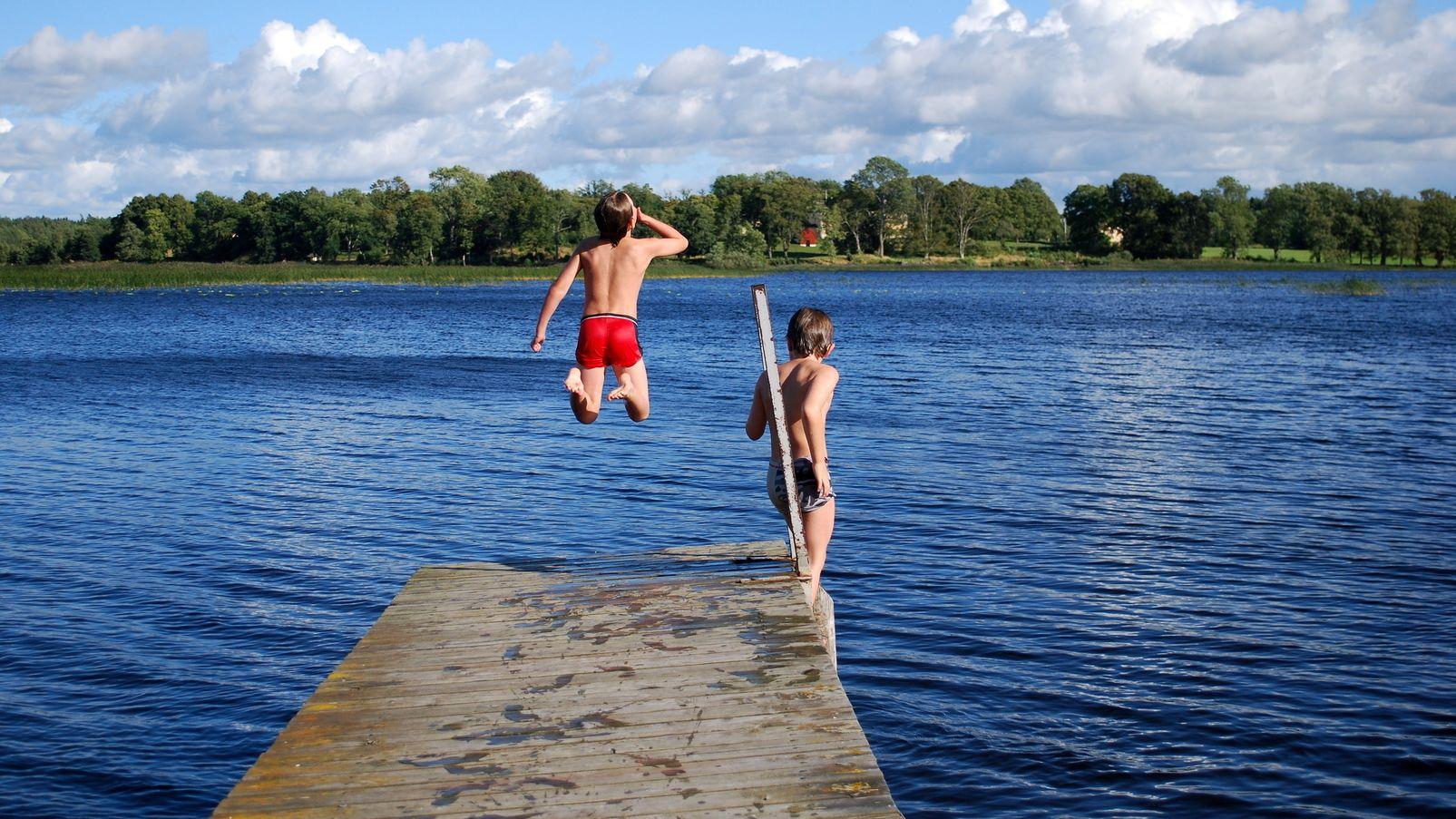 Zwei Jungen an einem Badesee springen von einem Steg aus ins Wasser.