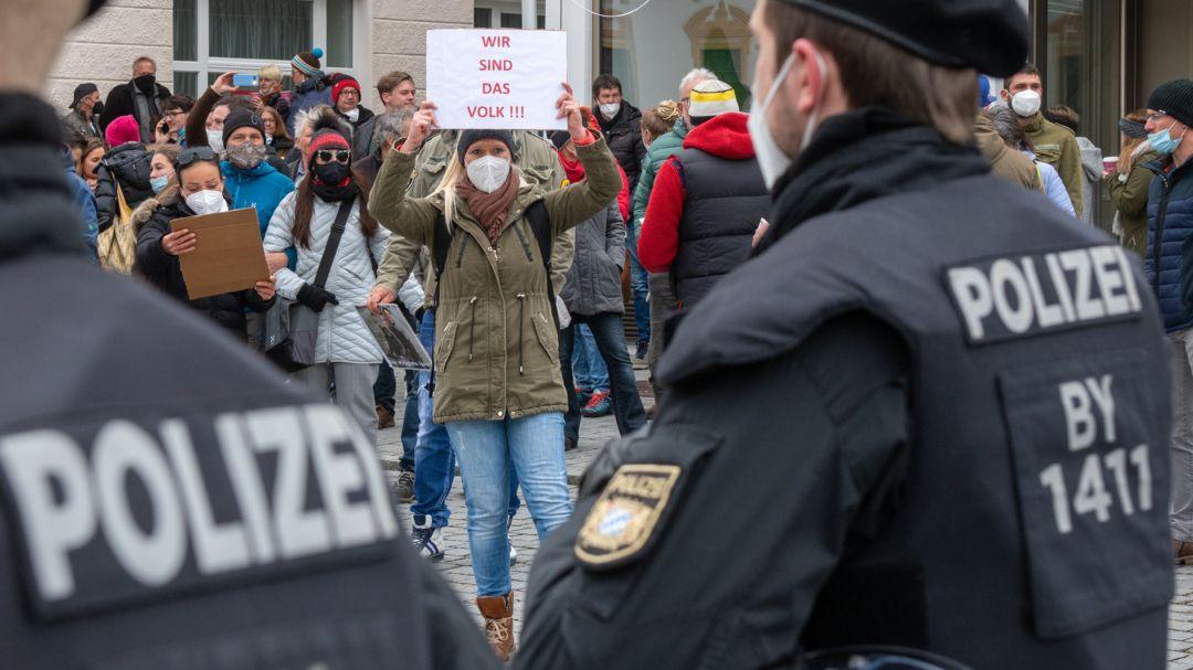 """Eine Frau hält Polizisten ein Schild mit der Aufschrift """"Wir sind das Volk"""" entgegen."""